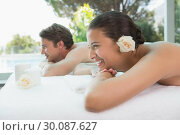 Купить «Couple lying on massage table at spa center», фото № 30087627, снято 8 апреля 2014 г. (c) Wavebreak Media / Фотобанк Лори