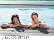 Купить «Smiling young couple in swimming pool», фото № 30087727, снято 8 апреля 2014 г. (c) Wavebreak Media / Фотобанк Лори