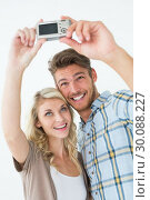Купить «Attractive young couple taking a selfie together», фото № 30088227, снято 29 апреля 2014 г. (c) Wavebreak Media / Фотобанк Лори