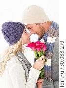 Купить «Attractive couple in warm clothing holding flowers», фото № 30088279, снято 29 апреля 2014 г. (c) Wavebreak Media / Фотобанк Лори