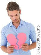 Купить «Young man holding broken heart», фото № 30088315, снято 29 апреля 2014 г. (c) Wavebreak Media / Фотобанк Лори