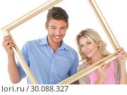 Купить «Attractive couple smiling at camera through picture frame», фото № 30088327, снято 29 апреля 2014 г. (c) Wavebreak Media / Фотобанк Лори
