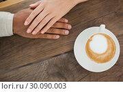 Купить «Couple holding hands beside cappuccino», фото № 30090003, снято 13 февраля 2014 г. (c) Wavebreak Media / Фотобанк Лори