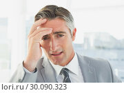 Купить «Businessman suffering from a headache», фото № 30090323, снято 6 мая 2014 г. (c) Wavebreak Media / Фотобанк Лори