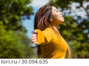Купить «Beautiful woman with arms outstretched in park», фото № 30094635, снято 4 июня 2014 г. (c) Wavebreak Media / Фотобанк Лори