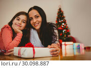 Festive mother and daughter smiling at camera. Стоковое фото, агентство Wavebreak Media / Фотобанк Лори