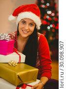 Купить «Festive brunette smiling at camera», фото № 30098907, снято 24 июля 2014 г. (c) Wavebreak Media / Фотобанк Лори