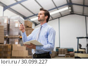 Купить «Manager holding clipboard in warehouse», фото № 30099227, снято 6 сентября 2014 г. (c) Wavebreak Media / Фотобанк Лори