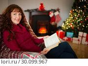 Купить «Cheerful redhead reading on the armchair at christmas», фото № 30099967, снято 3 октября 2014 г. (c) Wavebreak Media / Фотобанк Лори