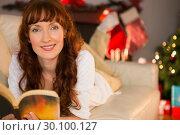 Купить «Pretty woman lying on a cosy couch reading book», фото № 30100127, снято 3 октября 2014 г. (c) Wavebreak Media / Фотобанк Лори