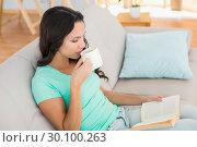 Купить «Woman reading and drinking coffee on couch», фото № 30100263, снято 2 октября 2014 г. (c) Wavebreak Media / Фотобанк Лори