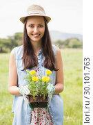 Купить «Happy woman holding potted flowers», фото № 30101763, снято 11 ноября 2014 г. (c) Wavebreak Media / Фотобанк Лори