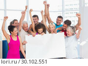 Excited people holding blank billboard at gym. Стоковое фото, агентство Wavebreak Media / Фотобанк Лори