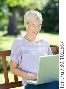 Купить «Smiling blonde using laptop in a park», фото № 30102567, снято 17 ноября 2014 г. (c) Wavebreak Media / Фотобанк Лори