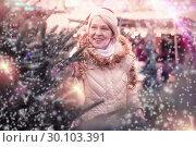Купить «Mature female buying decoration and tree at Christmas Fair», фото № 30103391, снято 21 декабря 2017 г. (c) Яков Филимонов / Фотобанк Лори