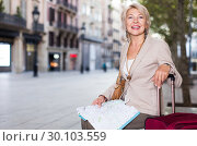 Купить «Adult woman 50-60 years old is sitting with map and suitcase», фото № 30103559, снято 3 сентября 2017 г. (c) Яков Филимонов / Фотобанк Лори