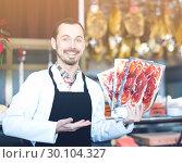 Купить «Seller offering sliced bacon», фото № 30104327, снято 2 января 2017 г. (c) Яков Филимонов / Фотобанк Лори