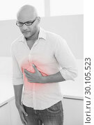 Casual man suffering from chest pain at home. Стоковое фото, агентство Wavebreak Media / Фотобанк Лори