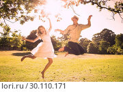 Купить «Cute couple jumping in the park together», фото № 30110171, снято 31 января 2014 г. (c) Wavebreak Media / Фотобанк Лори