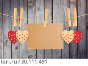 Купить «Composite image of hearts hanging on line with card», фото № 30111491, снято 23 января 2015 г. (c) Wavebreak Media / Фотобанк Лори