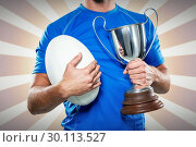 Composite image of rugby player holding trophy and ball. Стоковое фото, агентство Wavebreak Media / Фотобанк Лори