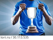Composite image of mid section of sportsman holding trophy. Стоковое фото, агентство Wavebreak Media / Фотобанк Лори