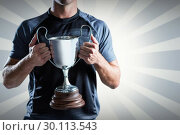 Composite image of victorious rugby player holding trophy. Стоковое фото, агентство Wavebreak Media / Фотобанк Лори