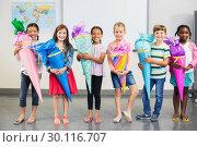 Купить «Happy kids holding gifts in classroom», фото № 30116707, снято 5 марта 2016 г. (c) Wavebreak Media / Фотобанк Лори