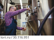 Manufacturer filling beer from storage tank at brewery. Стоковое фото, агентство Wavebreak Media / Фотобанк Лори