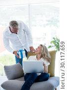 Купить «Man giving gift to woman holding laptop», фото № 30117659, снято 3 февраля 2016 г. (c) Wavebreak Media / Фотобанк Лори
