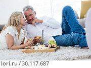 Купить «Romantic couple with white wine and food while lying on rug», фото № 30117687, снято 3 февраля 2016 г. (c) Wavebreak Media / Фотобанк Лори