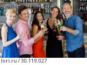 Group of friends holding glass of champagne flute and bottle. Стоковое фото, агентство Wavebreak Media / Фотобанк Лори