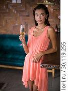 Portrait of confident woman holding a champagne flute. Стоковое фото, агентство Wavebreak Media / Фотобанк Лори