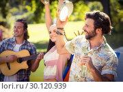 Купить «Man holding beer bottle and playing tambourine», фото № 30120939, снято 20 июля 2016 г. (c) Wavebreak Media / Фотобанк Лори