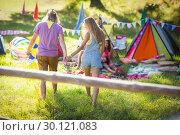 Купить «Couple holding hands and walking near campsite», фото № 30121083, снято 20 июля 2016 г. (c) Wavebreak Media / Фотобанк Лори