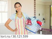 Купить «Composite image of happy woman with laundry basket», фото № 30121599, снято 15 сентября 2016 г. (c) Wavebreak Media / Фотобанк Лори