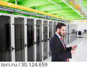 Купить «Businessman using digital tablet against database server systems in background», фото № 30124659, снято 8 декабря 2016 г. (c) Wavebreak Media / Фотобанк Лори