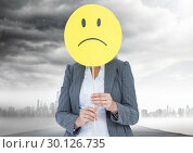 Купить «Businesswoman holding a smiley face in front of her face with rain clouds in background», фото № 30126735, снято 23 декабря 2016 г. (c) Wavebreak Media / Фотобанк Лори