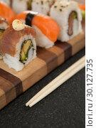 Купить «Assorted sushi set served with chopsticks on wooden board», фото № 30127735, снято 8 декабря 2016 г. (c) Wavebreak Media / Фотобанк Лори