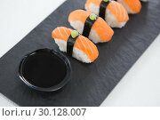 Купить «Close-up of nigiri sushi served on black stone slate», фото № 30128007, снято 8 декабря 2016 г. (c) Wavebreak Media / Фотобанк Лори