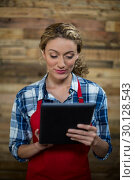 Купить «Waitress using digital tablet against wooden wall», фото № 30128543, снято 12 октября 2016 г. (c) Wavebreak Media / Фотобанк Лори