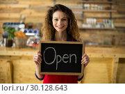 Купить «Smiling waitress showing slate with open sign in café», фото № 30128643, снято 12 октября 2016 г. (c) Wavebreak Media / Фотобанк Лори