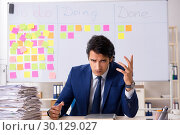 Купить «Young handsome employee in front of whiteboard with to-do list», фото № 30129027, снято 16 октября 2018 г. (c) Elnur / Фотобанк Лори