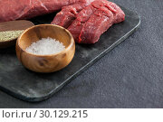Купить «Beef steak, salt and spices on black slate plate», фото № 30129215, снято 20 сентября 2016 г. (c) Wavebreak Media / Фотобанк Лори