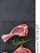 Купить «Rib chop and herb on black slate plate», фото № 30129227, снято 20 сентября 2016 г. (c) Wavebreak Media / Фотобанк Лори