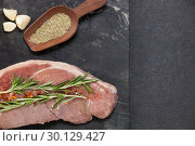 Купить «Sirloin chop, garlic and spices on black slate plate», фото № 30129427, снято 20 сентября 2016 г. (c) Wavebreak Media / Фотобанк Лори