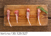 Купить «Rib chop and rosemary herb on on wooden tray against wooden background», фото № 30129527, снято 20 сентября 2016 г. (c) Wavebreak Media / Фотобанк Лори