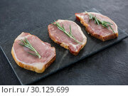 Купить «Sirloin chops and rosemary herb on slate plate», фото № 30129699, снято 20 сентября 2016 г. (c) Wavebreak Media / Фотобанк Лори