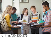 Купить «Group of smiling students standing with notebook in corridor», фото № 30130375, снято 19 ноября 2016 г. (c) Wavebreak Media / Фотобанк Лори