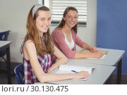 Купить «Portrait of happy schoolgirls sitting in classroom», фото № 30130475, снято 19 ноября 2016 г. (c) Wavebreak Media / Фотобанк Лори
